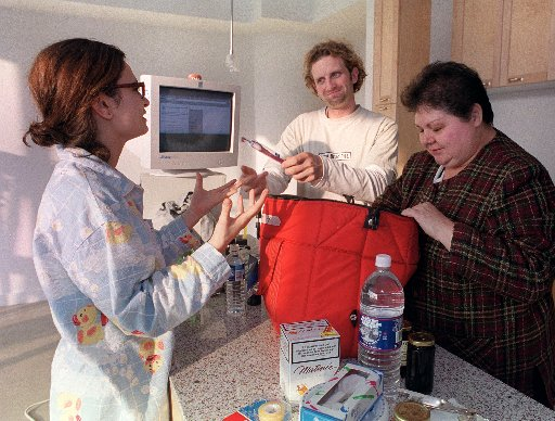 Gavin McGarry, 30, hands Helen Goltsios (left) , 27, a toothbrush from the bag of groceries they ordered online from Jeninne Plant (right) at The Peach Tree website on Tuesday, November 23, 1999. The pair put their lives on hold for one week to participate in an Internet project whereby the pair, previously strangers, live in a downtown Toronto loft for five days  with nothing but a credit card and internet access.  (CP PHOTO/ Yvonne Berg)
