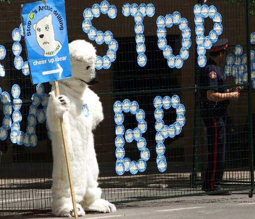 A protester dressed as a polar bear stands outside the World Petroleum Congress barricade which  stickers were placed on Tuesday June 13, 2000 in Calgary in protest of BPs arctic drilling.  BP Amoco Group Chief Executive Sir John Browne participated in the World Petroleum Congress Tuesday morning. (CP PHOTO/Adrian Wyld)