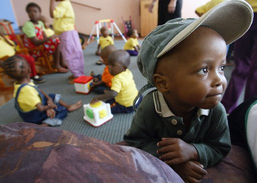 Four-year-old  AIDS orphan  Andries looks away while other AIDS orphans play in the orphanage ward at the Kalfong Hospital in Pretoria South Africa Sunday April 7, 2002. All of the orphans either have or run the risk of developing AIDS contracted from their deceased parents. It is estimated that over 4.7 million South Africans are HIV-positive.(CP PHOTO/Tom Hanson)