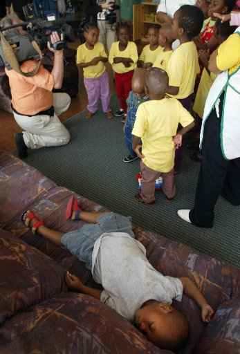 Three-year-old  AIDS orphan Vincent,  with a life expectancy of another eight months, sleeps on a couch as he is too ill to participate in a sing-along by other orphans for visiting media at the orphanage ward at the Kalfong Hospital in Pretoria South Africa Sunday April 7, 2002. All of the orphans either have or run the risk of developing AIDS contracted from their deceased parents. It is estimated that over 4.7 million South Africans are HIV-positive.(CP PHOTO/Tom Hanson)