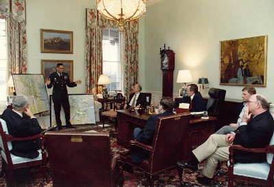 President Bush participates in a briefing on the progress of the ground war with Iraq in his residence office. General Powell points out areas on two maps of the Middle East. Also present are: Secretary Cheney, Robert Gates, Secretary Baker, Governor Sununu and Vice President Quayle