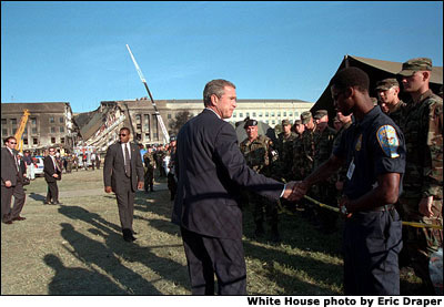 President George W. Bush is seen infront of the terrorist-damaged Pentagon building, thanking rescue workers for their efforts.