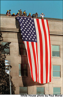 Firefighers unfurl the United States flag over the damaged Pentagon building after terrorists attacked the building on September 11, 2001.