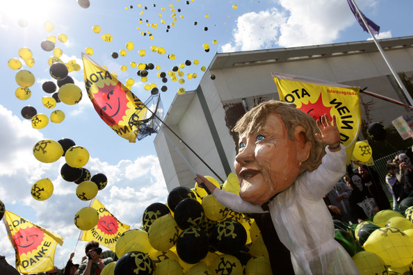 Government Leaders Meet Over Nuclear Energy Policy: BERLIN - SEPTEMBER 05:  An activist wearing an effigy of German Chancellor Angela Merkel attempts to catch escaping balloons meant to represent leaking radiation as he stands among anti-nuclear protesters demonstrating outside the Chancellery on September 5, 2010 in Berlin, Germany. Merkel and leading members of her government coalition were meeting in the Chancellery to decide by how much to prolong the working life of Germany's 15 nuclear power plants. Merkel claims she is committed to the large-scale development of renewable energy sources such as solar and wind, though argues that the prolongation of atomic power is necessary as a temporary measure.  (Photo by Sean Gallup/Getty Images)