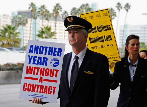 United Airlines Flight Attendants Demonstrate Against Company's Stance On Contract Negotiations: LOS ANGELES, CA - JANUARY 07:  United Airlines workers, represented by the Association of Flight Attendants-CWA, AFL-CIO, picket at the United Airlines terminal at Los Angeles International Airport on January 7, 2011 in Los Angeles, California. The protest was part of a world-wide response over the stalled contract negotiations.  (Photo by Kevork Djansezian/Getty Images)