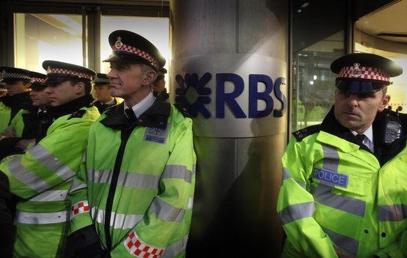 The Right To Work Campaigners Demonstrate Outside Of Royal Bank Of Scotland Offices: LONDON, ENGLAND - JANUARY 14:  Policeman stand at the entrance to the Royal Bank of Scotland HQ on January 14, 2011 in London, England.  Protestors have called for the sacking of RBS bank Chief Executive Stephen Hester as RBS prepares to give B#1 billion in bonus payments to staff despite yesterday being fined B#2.8 million over it's customer service record. Hester himself is potentially in-line for a B#3 million bonus payment.  (Photo by Peter Macdiarmid/Getty Images)