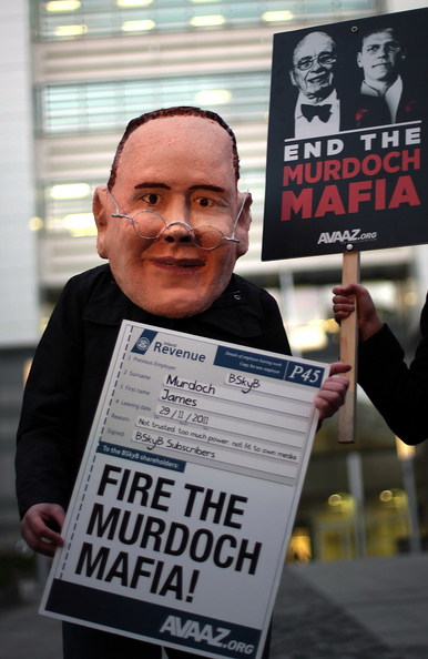 LONDON, ENGLAND - FEBRUARY 29: A protestor from the AVAAZ campaigning group wears a mask depicting James Murdoch outside the headquarters of News International on February 29, 2012 in London, England. James Murdoch has announced that he is stepping down from his role as executive chairman of News International the publishers of the Sun and The Sunday Times newspapers.  (Photo by Peter Macdiarmid/Getty Images)