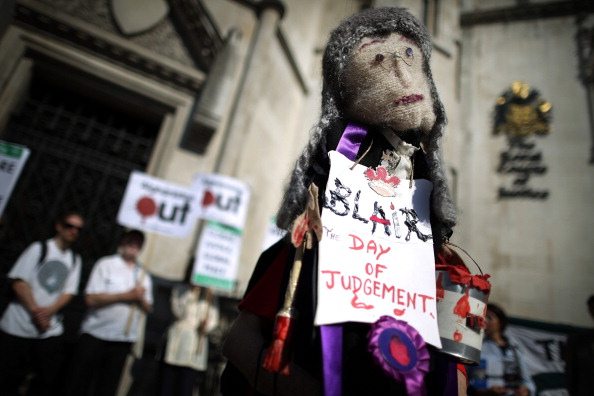 LONDON, ENGLAND - MAY 28:  A doll of Former Prime Minister Tony Blair is held aloft by an anti-war protestor outside The Royal Courts of Justice as Mr Blair started to give evidence to the Leveson Inquiry on May 28, 2012 in London, England. This phase of the inquiry into the culture, practice and ethics of the press in the United Kingdom is looking at the relationship between the press and politicians. The inquiry, which may take a year or more to complete, comes in the wake of the phone hacking scandal that saw the closure of The News of The World newspaper in 2011.  (Photo by Peter Macdiarmid/Getty Images)