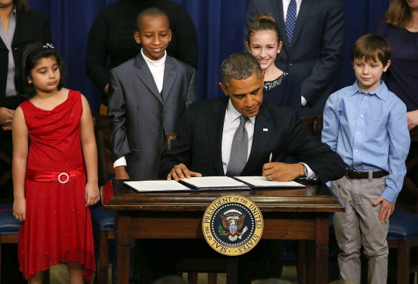 Obama And Biden Unveil Proposal To Decrease Gun Violence In U.S.: WASHINGTON, DC - JANUARY 16:  U.S. President Barack Obama signs a series of executive orders about the administration's new gun law proposals as children who wrote letters to the White House about gun violence, (L-R) Hinna Zeejah, Taejah Goode, Julia Stokes and Grant Fritz, look on in the Eisenhower Executive Office building, on January 16, 2012 in Washington, DC. One month after a massacre that left 20 school children and 6 adults dead in Newtown, Connecticut, the president unveiled a package of gun control proposals that include universal background checks and bans on assault weapons and high-capacity magazines.  (Photo by Mark Wilson/Getty Images)