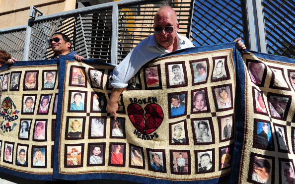 US-RELIGION-CATHOLIC-ABUSE: Abuse victim Jorgen Olsen (R) and supporter Glenn Gorospa (L) hold quilts bearing portraits of abused children while gathered outside the Cathedral of Our Lady of the Angels in Los Angeles, California, on February 1, 2013, one day after the release of personnel files of priests accused of sexual misconduct. The archbishop of Los Angeles Jose Gomez stripped his predecessor, retired Cardinal Roger Mahony, of all church duties on January 31. In all, 124 files were released on the Los Angeles archdiocese's website, listed by priests' names, including 82 containing information on allegations of childhood sexual abuse.   AFP PHOTO / Frederic J. BROWN        (Photo credit should read FREDERIC J. BROWN/AFP/Getty Images)