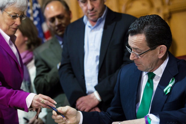 CT Gov. Dannel Malloy Signs Broad Gun Control Bill: HARTFORD, CT - APRIL 4:  Connecticut, Lieutenant Gov. Nancy Wyman (L) takes a pen from Connecticut Gov. Dannel Malloy (R) as he signs a gun-control bill at the Connecticut Capitol April 4, 2013 in Hartford, Connecticut. After more than 13 hours of debate, the Connecticut General Assembly approved the gun-control bill early April 4, that proponents see as the toughest-in-the-nation response to the Demember 14, 2012 Newtown school shootings. (Photo by Christopher Capozziello/Getty Images)