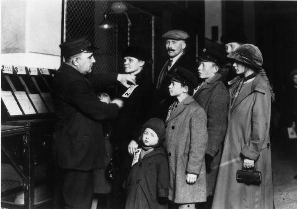 On Ellis Island-A customs official attaches labels to the coats of a German immigrant family at the Registry Hall on Ellis Island, New York City.   (Photo by Lewis W Hine/Getty Images)  -- Image Date: 01/01/1905  -- Image Date: 01/01/1905