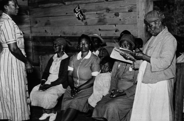 Reading Aloud Juanita Coleman, a teacher and National Youth Administration leader, listening as one of her pupils in the adult class reads aloud.   (Photo by Marion Post Wolcott/Getty Images)  -- Image Date: 01/05/1939  -- Image Date: 01/05/1939