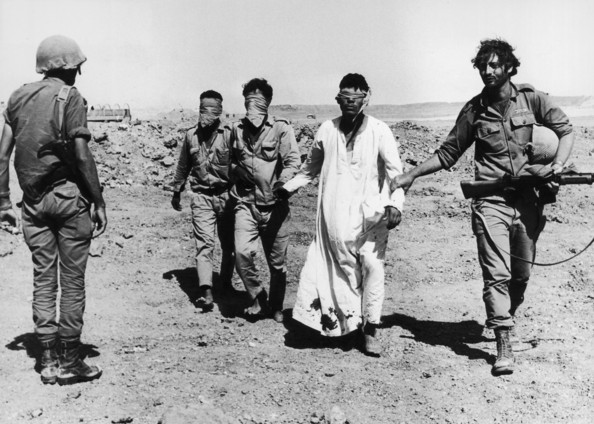 Yom Kippur POWs Three barefoot, blindfolded Egyptian POWs are led to the western side of the Suez Canal by an Israeli soldier as another soldier looks on during the Yom Kippur War, Middle East. One of the POWs wears a long, blood-stained dishdash or Kaftan. Israel retained control of its territories in the conflict.   (Photo by Daniel Rosenblum/Getty Images)  -- Image Date: 29/10/1973  -- Image Date: 29/10/1973