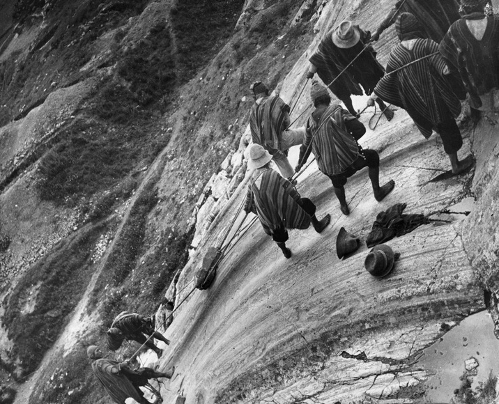 circa 1950:  Peruvian workers demonstrate how the ancient Incas polished the large surfaces of their stone buildings, by hauling a rough boulder back and forth across the rock face.  (Photo by Kurt Severin/Hulton Archive/Getty Images)