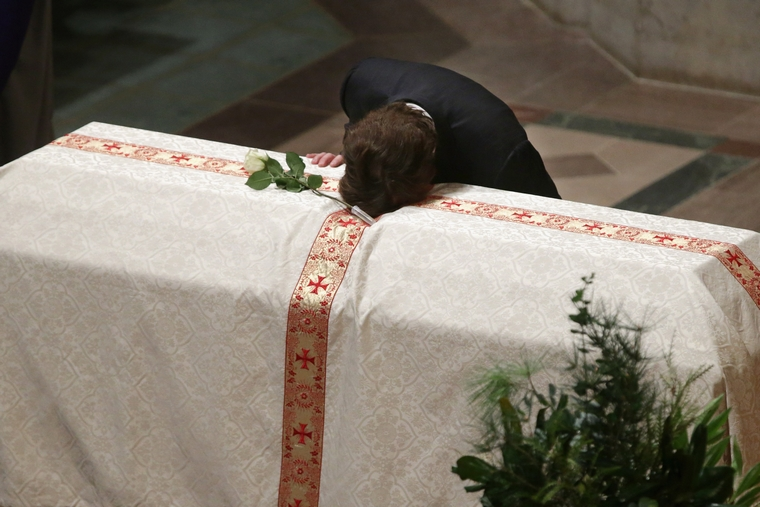 WASHINGTON, DC - OCTOBER 29:  Quinn Bradlee puts he head on the casket of his father and former Washington Post Executive Editor Ben Bradlee at the Washington National Cathedral October 29, 2014 in Washington, DC. Bradlee died at his home in Georgetown October 21, 2014 at the age of 93. Bradlee was at the helm of the newspaper from 1968 to 1991, during which time it published the Pentagon Papers and stories documenting the Watergate scandal, leading to the resignation of President Richard Nixon.  (Photo by Chip Somodevilla/Getty Images)