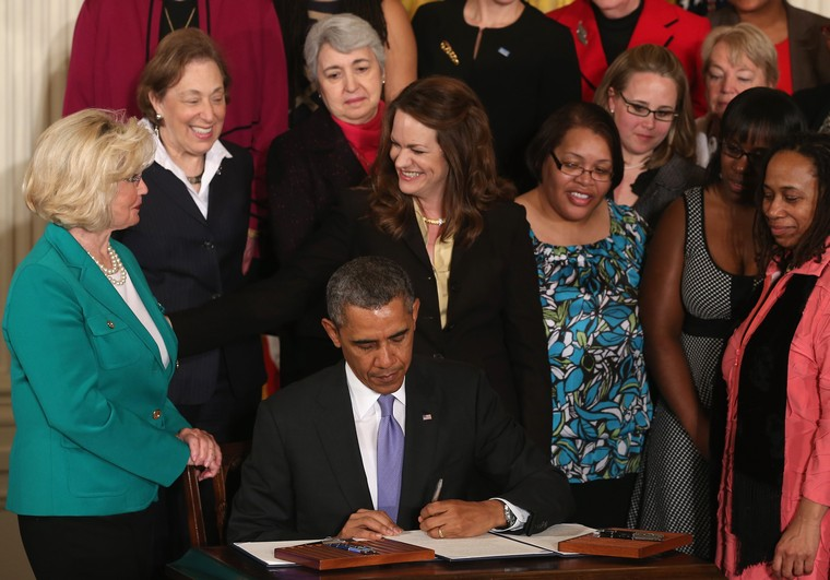 WASHINGTON, DC - APRIL 08:  U.S. President Barack Obama is flanked by Lilly Ledbetter (L) and other women while signing an executive order banning federal contractors from retaliating against employees during an event in the East Room of the White House in honor of