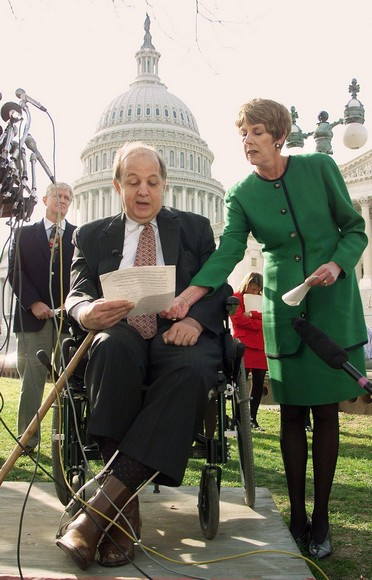 WASHINGTON, :  Gun control advocates, former White House Press Secretary Jim Brady (L) and his wife Sarah (R) speak to reporters 30 November outside the US Capitol about the 30 November expiration of a five-day waiting period for the purchase of a handgun. Brady, who is in a wheelchair as a result of being shot during an assassination attempt on former US President Ronald Reagan in 1981,  said the new instant background check is flawed and will allow more guns into the hands of criminals and people who shouldn't have them. US Rep. Jim Moran, D-VA, is behind at left.       (ELECTRONIC IMAGE)    AFP PHOTO/Luke FRAZZA (Photo credit should read LUKE FRAZZA/AFP/Getty Images)