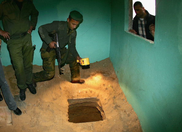 Photo Title: Palestinian Security Destroy Weapons Smuggling Tunnels -- RAFAH REFUGEE CAMP, GAZA STRIP - MARCH 7:  A Palestinian security officer overlooks a discovered tunnel next to the border wall between Egypt and Rafah refugee camp on March 7, 2005 as part of Palestinian crackdown on arms smuggling in the southern Gaza Strip .The tunnels, often used by terrorist groups to smuggle weapons from Egypt into the Gaza Strip, have long been demanded by Israel to be destroyed by the Palestinian security forces.  (Photo by Abid Katib/Getty Images)  -- Image Date: 07/03/2005  -- Image Date: 07/03/2005