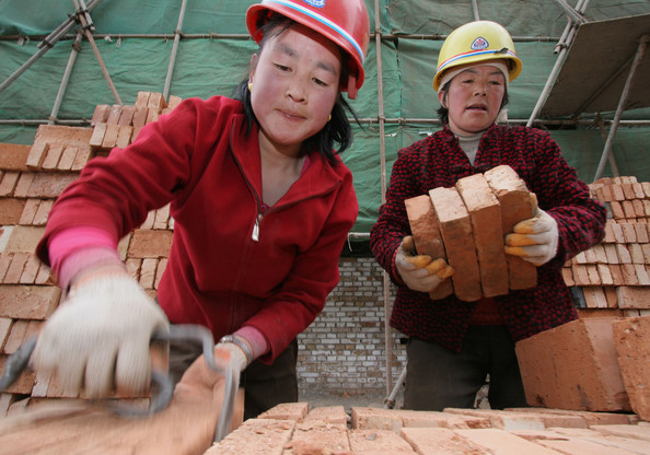 Photo Title: Migrant Workers' Plight Causes Concern In China -- XINING, CHINA - APRIL 5: (CHINA OUT) Women migrant workers remove bricks at a construction site on April 5, 2005 in Xining of Qinghai Province, China. Premier Wen Jiabao admitted China faced