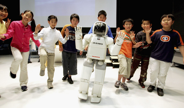 Photo Title: Honda Offers ASIMO To Science Classes -- TOKYO, JAPAN - APRIL 6: Honda's walking robot ASIMO balances together with Japanese Grade 6 students, during a press conference to explain ?The National Museum of Emerging Science and Innovation (MeSci) ASIMO Science Class? at the MeSci on April 6, 2005 in Tokyo, Japan. Honda will contribute to science programs to be conducted by the MeSci for students of grades 1-9 by helping develop and implement programs utilizing their humanoid robot ASIMO. The programs will teach science from the perspective of the robot, teaching the teachers as well as the students as the teachers will have to learn to control the robot.  Programs will start from this school year in Japan.  (Photo by Junko Kimura/Getty Images)  -- Image Date: 06/04/2005  -- Image Date: 06/04/2005
