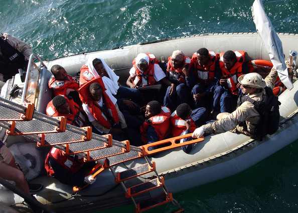 Photo Title: US And German Navy Rescue Fisherman -- GULF OF ADEN - APRIL 29: In this handout photo released on May 2, 2005, sailors assigned to the guided missile cruiser USS Normandy and the coastal patrol ships USS Typhoon and USS Firebolt transfer men and women in a rigid hull inflatable boat after their boat, a fishing vessel, capsized 25 miles on April 29, 2005, off the coast of Somalia. The German Navy frigate FGS Karlsruhe also assisted in the rescue effort. Eighty-nine people survived the incident, with 5 pronounced dead on the scene. (Photo by Robert R. McRill/US Navy via Getty Images)  -- Image Date: 29/04/2005  -- Image Date: 29/04/2005