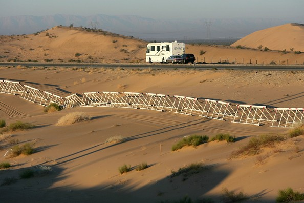 WINTERHAVEN, CA - OCTOBER 08:  A vehicle-proof barrier now lines the south side of Interstate 8 at the Imperial Dunes, a short distance north of the US-Mexico border where no fence divides the two nations, October 8, 2006 west of Winterhaven, California. US Fish and Wildlife Service wardens and environmentalists warn that a proposed plan by US lawmakers to construct 700 miles of double fencing along the 2,000-mile US-Mexico border, in an attempt to wall-out illegal immigrants, would also harm rare wildlife.  Wildlife experts say cactus-pollinating insects would fly around fence lights, birds that migrate by starlight in the desert wilderness would be confused, and large mammals such as jaguars, Mexican wolves, Sonoran pronghorn antelope, and desert bighorn sheep would be blocked from migrating across the international border, from California to Texas.  (Photo by David McNew/Getty Images)  -- Image Date: 10/8/2006  -- Image Date: 10/8/2006
