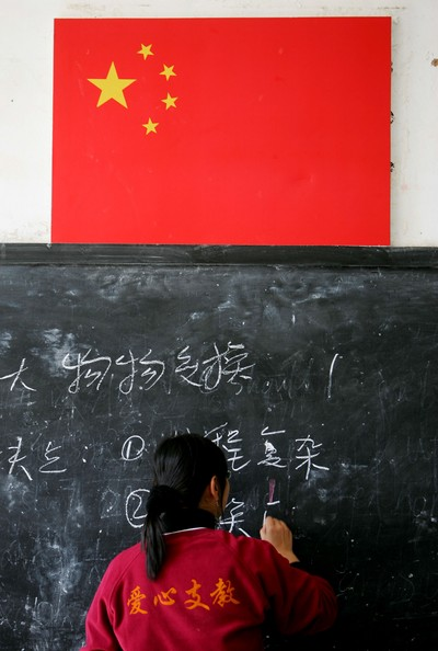 NYINGCHI COUNTY, CHINA - OCTOBER 28: (CHINA OUT) A volunteer teacher writes on a blackboard during a class at Nyingchi First High School, the only high school of Nyingchi Prefecture, on October 28, 2006 in Nyingchi County of Tibet Autonomous Region, China. Graduates from important universities volunteered to teach in China's western provinces such as Ningxia Hui, Tibet, Inner Mongolia autonomous regions and Yunnan Province. The one-year placement was started from 1999 by China's Ministry of Education and Communist Youth League of China. (Photo by China Photos/Getty Images)  -- Image Date: 10/28/2006  -- Image Date: 10/28/2006