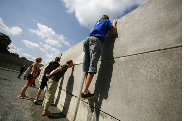 Documents Confirms Shoot To Kill At Berlin Wall: BERLIN - AUGUST 13: A young man climbs up an inner wall at a still-standing portion of the Berlin Wall at Bernauer Street on the 46th anniversary of construction of the Berlin Wall August 13, 2007 in Berlin, Germany. Authorities in the eastern German city of Magdeburg recently discovered a 1973 document of the former East German internal security agency, the Stasi, giving guards at border posts the order to shoot anyone trying to flee the country, even women and children. The document confirms that shooting escapees was an official policy of the former East German government, something former East German politicians have long denied. Over a thousand East Germans died while attempting to escape East Germany for the West.   (Photo by Carsten Koall/Getty Images)  -- Image Date: 8/13/2007