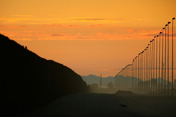 Construction Of Fence Along Mexican Border Picks Up Speed: SAN LUIS, AZ - OCTOBER 04:  Towering light poles and a wall of metal (L) recently constructed by National Guardsmen form a double-fence border barrier in a dusty no-man?s land of denuded desert that runs along the US-Mexico border on October 4, 2007 east of San Luis, California. Recent US federal construction of border fences has rapidly sped up. The sudden acceleration marks a change from a month ago when the Department of Homeland Security (DHS) announced that it would have only completed 15 of 70 miles of new fencing promised by the end of September, enraging anti-illegal-immigration groups and many Republicans. Instead, the DHS reached its goal of 70 miles to raise the total amount of border fences from 75 to about 145 miles. The fence-building frenzy is the result of the controversial Secure Fence Act, passed last fall, calling for 698 miles of border fences. Critics argue that extensive fencing will damage fragile desert environments, divide border neighborhoods, and that illegal immigrants will continue to find ways over, under, and through the fence or simply go around it elsewhere along the 2000-mile-long international border. Supporters believe that it will hinder border crossers.  (Photo by David McNew/Getty Images)  -- Image Date: 10/4/2007