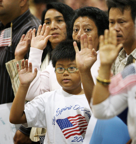 Thousands Of People Become US Citizens At Mass Naturalization Ceremony: LOS ANGELES, CA - AUGUST 28:  People take the oath of citizenship as 18,418 people are sworn in as US citizens during naturalization ceremonies at the Los Angeles Convention Center on August 28, 2008 in Los Angeles, California. Immigrants, especially Latinos, which now make up 15 percent of the US population, play an increasingly important role in US politics. Democratic presidential candidate Barack Obama (D-IL), who could benefit from a strong Hispanic following of former presidential hopeful Sen. Hillary Clinton (D-NY), who now campaigns for him, has set aside $20 million for Latino outreach. Republican rival John McCain has also stepped up efforts to attract Latinos, focusing particularly on those in the military. The US Department of Homeland Security reports that citizenship applications have jumped by more than 100 percent since 2006, a surge in naturalization that is expected to add to the 17 million existing eligible Latino voters nationwide and lead to an anticipated record of 9.2 million Latinos voting in the November presidential election. Issues of interest to Latinos include the slumping economy, employment, health care, housing, and immigration reform.  (Photo by David McNew/Getty Images)