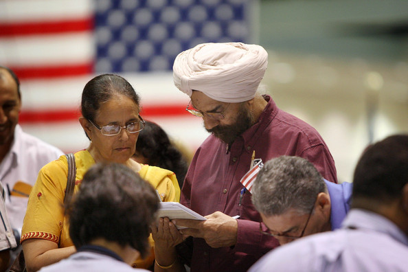Thousands Of People Become US Citizens At Mass Naturalization Ceremony: LOS ANGELES, CA - AUGUST 28:  Amrik Sidhu (R) and his wife Harjinder Sidhu, both Sikhs from India, apply for their passports after gaining US citizenship as 18,418 people are sworn in as US citizens during naturalization ceremonies at the Los Angeles Convention Center on August 28, 2008 in Los Angeles, California. Immigrants, especially Latinos, which now make up 15 percent of the US population, play an increasingly important role in US politics. Democratic presidential candidate Barack Obama (D-IL), who could benefit from a strong Hispanic following of former presidential hopeful Sen. Hillary Clinton (D-NY), who now campaigns for him, has set aside $20 million for Latino outreach. Republican rival John McCain has also stepped up efforts to attract Latinos, focusing particularly on those in the military. The US Department of Homeland Security reports that citizenship applications have jumped by more than 100 percent since 2006, a surge in naturalization that is expected to add to the 17 million existing eligible Latino voters nationwide and lead to an anticipated record of 9.2 million Latinos voting in the November presidential election. Issues of interest to Latinos include the slumping economy, employment, health care, housing, and immigration reform.  (Photo by David McNew/Getty Images)