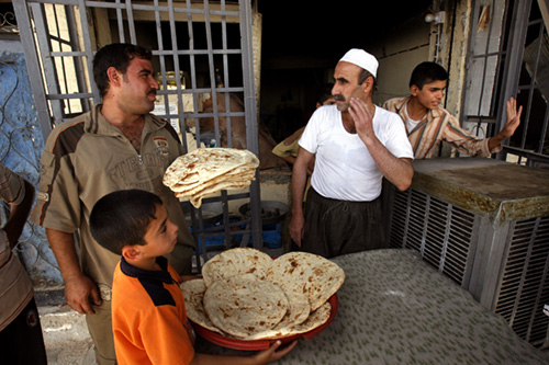 IRAQ, MOSUL - JULY 10: Iraqi baker Harath Mustafa (2-R) speaks to customers outside his store, July 10, 2008, in Mosul, Iraq.  Iraqi officials declared Mosul the last urban stronghold of Al Qaeda in Iraq. Only months ago, Mosul was the communication and supply hub for Al Qaeda and other insurgent groups from the Syrian border to central Iraq before US and Iraqi forces pushed them into the rural, desert areas where they are believed to be regrouping in the western Jazeera desert. With the upcoming provincial elections in autumn, Iraqis and Americans are bracing themselves for renewed violence. Since early 2008, Iraq's security situation has improved with oil production increasing, record government surplus and easing sectarian tensions. (Photo by Warrick Page/Getty Images)