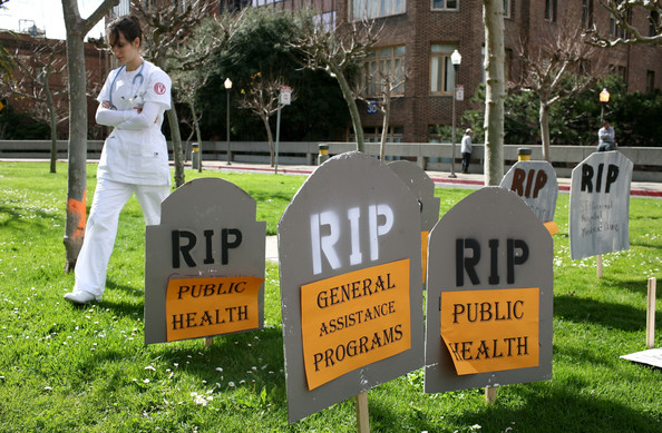 Health Care Workers Protest Funding Cuts To Public Health Department: SAN FRANCISCO - FEBRUARY 26:  A doctor walks through a mock graveyard during a rally with health care workers February 26, 2009 in San Francisco, California.  Dozens of San Francisco health care workers rallied outside of San Francisco General Hospital to protest San Francisco Mayor Gavin Newsom's deep cuts to the SF Department of Public Health tha has led to many employee layoffs.  (Photo by Justin Sullivan/Getty Images)
