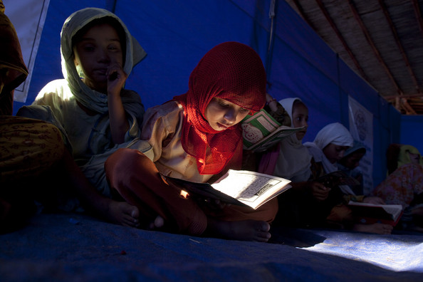 Internally Displaced Face Harsh Conditions In Relief Camps: SWABI, PAKISTAN - JUNE 20:  A Pakistani girl reads her book during a 3 hour religious class at the Ummah Welfare Trust madrassa (religious school) on June 20, 2009 in the Chota Lahore relief camp in Swabi, Pakistan. Over 1.9 million internally displaced persons are living at internally displaced people (IDP) camps as a result from recent fighting and on-going military operations against the Taliban. Pakistani forces battled militants in tribal areas after vowing an full assault on a Taliban chief in the lawless Afghan border region known to be an Al-Qaeda hideout. In the cleared areas such as Buner many families are waiting to return but are currently still waiting for basic facilities like electricity and water before most leave the camps.  (photo by Paula Bronstein /Getty Images)