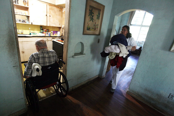Subsidized Long-Term Care Supporters See Opportunity With Health Care Bill: MIAMI - DECEMBER 14:  United HomeCare Services home health aide Wendys Cerrato carries bedding to the washing machine as she helps Robert Granville in his home on December 14, 2009 in Miami, Florida. The U.S. Senate continues to debate the need for the Community Living Assistance Services and Supports (CLASS) Act in the health care reform bill, which would provide a government-sponsored basic cash benefit to those needing long-term care services at home, in assisted living, or in a nursing facility. Without the help of United HomeCare Services Robert would be unable to continue to live on his own since he has limited mobility.  (Photo by Joe Raedle/Getty Images)