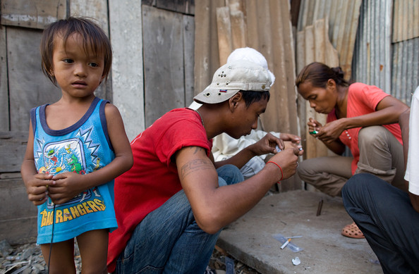 KHM: Heroin On The Streets Of Phnom Penh: PHNOM PENH, CAMBODIA - FEBRUARY 14:  (CAMBODIA AND THAILAND OUT)  Sok Pean (R) smokes heroin as her son, Thea, 2, waits February 14, 2010 in Phnom Penh, Cambodia.  Recently Human Rights Watch published a critical report on human rights abuses in many drug detention centers in Cambodia, where drug users have few places to turn for help with their addictions. Among other health issues, about 170,000 Cambodians live with HIV/AIDS and more than 60,000 children are orphaned by the disease. Impoverished Cambodia has become a popular trafficking point for narcotics, particularly methamphetamines and heroin, after neighboring Thailand toughened its war on drugs.  An estimated 36 per cent of Cambodia's 14.2 million people live below the poverty line and about 85 per cent of these live in rural areas.  (Photo by Paula Bronstein /Getty Images)