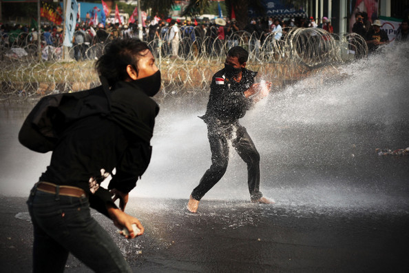 Indonesians Protest Over Government's Bank Century Bailout: JAKARTA, INDONESIA - MARCH 02:  Police hose protesters with a water cannon as they demonstrate outside the House of Representatives' inquiry into the Bank Century bailout at Jakarta's Parliament building on March 2, 2010 in Jakarta, Indonesia. The Parliamentary inquiry committee is due to report its recommendations in the Bank Century case, which saw now-Vice President Boediono, formerly Central bank governor at the time of the bailout, and Finance Minister Sri Mulyani Indrawati involved in what is being debated as an allegedly illegal bailout.  (Photo by Ulet Ifansasti/Getty Images)