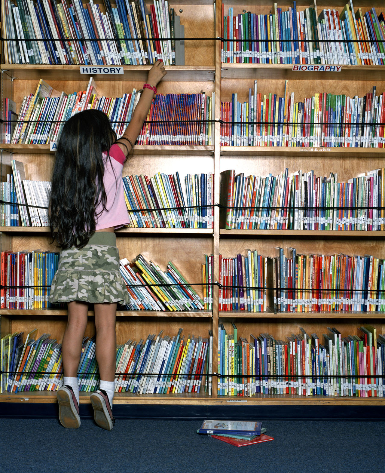 Girl (4-5 years) standing on tip toes reaching for book on library bookshelf, rear view