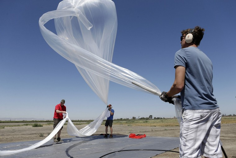 Project Loon members Bill Rogers, from left, T.J. Tierney and Michael Margraf slowly fill the balloon with helium as they prepare to launch a high-altitude balloon carrying electronic testing equipment into the skies above Dos Palos, California, Friday, July 26, 2013. The test launch is part of the research being done by the Google X division to create a high-altitude transponder network that will provide Internet access to underserved areas of the world. (Gary Reyes/Bay Area News Group/MCT)