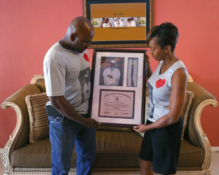 Miami Beach police officers Chris and Shantell Mitchell hold the high school diploma of their late son Dwayne on Friday, Aug. 19, 2016 in Miami. In March, the son of two Miami Beach police officers died from a rare heart condition called Wolff-Parkinson-White Syndrome, which could have been detected by an EKG. The parents have created an organization called the Dwayne Have A Heart Foundation to advocate for all children getting an EKG. (David Santiago/Miami Herald/TNS)