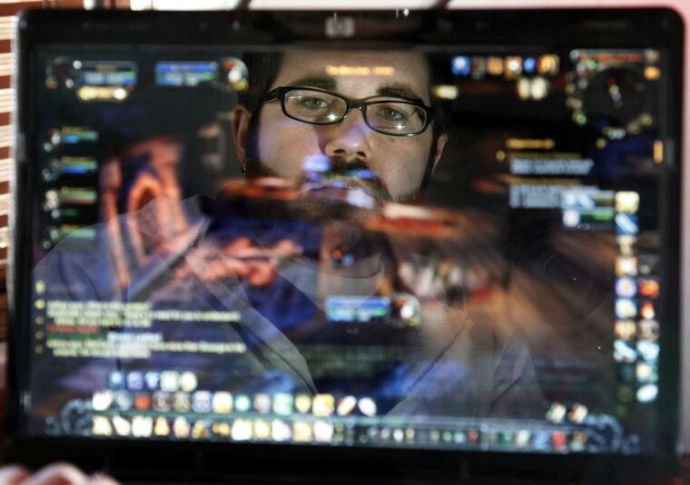 Joe Osborne is reflected in his computer monitor as he plays World of Warcraft, an online game, November 19, 2010, in Philadelphia, Pennsylvania.  (Laurence Kesterson/Philadelphia Inquirer/MCT)