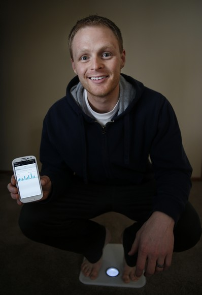 Jared Sieling of Maple Grove, Minnesota keeps close track on his health and fitness through electronics. He uses a scale that sends his weight and body fat to his smart phone and the phone also tracks the number of steps he takes each day. (Richard Tsong-Taatarii/Minneapolis Star Tribune/MCT)
