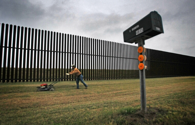 A resident on Oklahoma Avenue outside Brownsville, Texas mows the grass along the high steel border fence that's designed to thwart Mexican drug runners and illegal immigrant smugglers, January 20, 2011. In many places here in southeast Texas, the fence i