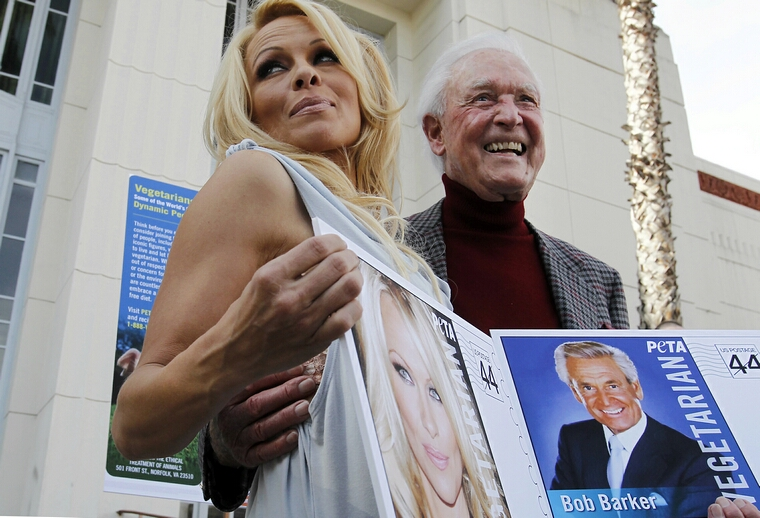 Celebrities and animal rights activists Pamela Anderson and Bob Barker pose for pictures and show off new PETA vegetarian postage stamps that feature their images on Tuesday, November 29, 2011, at the Hollywood Post Office in Los Angeles, California. The