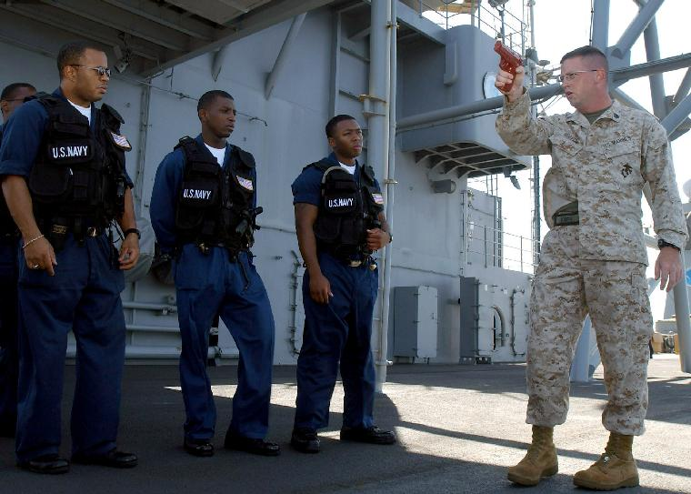 NAV2003040619 -  Gulf of Aden,  April 3  (UPI)  -- U.S. Marine Sgt. Gregory Hoover from Waverly, N.Y., instructs members of the security force aboard USS Mount Whitney (LCC/JCC 20) on proper gun-handling procedures.  The Mount Whitney is deployed to the Horn of Africa region, participating in Operation Enduring Freedom and the global war on terrorism.                     dg/Aida E. Miranda/U.S. Navy    UPI
