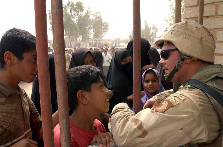 NAV2003040914-AL NAJAF, Iraq, April 8 (UPI)-- An Iraqi boy greets a U.S. Army soldier during an effort to distribute food and water to Iraqi citizens in need near Al Najaf, Iraq on April 8, 2003. The U.S. military is working with international relief organizations to help provide food and medicine for the Iraqi people in support of Operation Iraqi Freedom. Operation Iraqi Freedom is the multinational coalition effort to liberate the Iraqi people, eliminate Iraq's weapons of mass destruction and end the regime of Saddam Hussein.    jg/Arlo K. Abrahamson/U.S. Navy  UPI