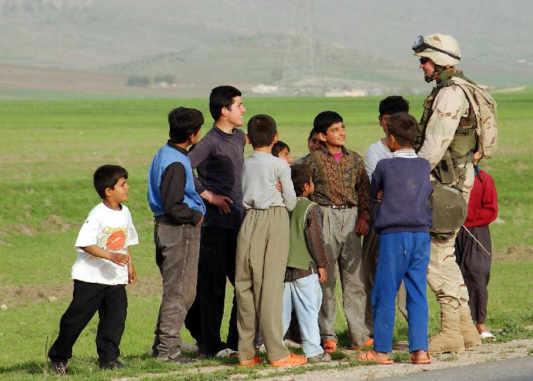 AFP2003041105-NORTHERN IRAQ, April 9 (UPI)-- Airman 1st Class Edward Crofoot, 100th Security Forces Squadron, Mildenhall Air Base, 86th Expeditionary Contingency Response Group, greets local children during a long halt listening post/observation post during patrol April 9 in support of Operation Iraqi Freedom.  Children and adults in this region have been supportive and friendly to the coalition forces here. Operation Iraqi Freedom is the multi-national coalition effort to liberate the Iraqi people, eliminate Iraqi's weapons of mass destruction and end the regime of Saddam Hussein.     jg/U.S. Air Force photo/Tech. Sgt Rich Pucket    UPI
