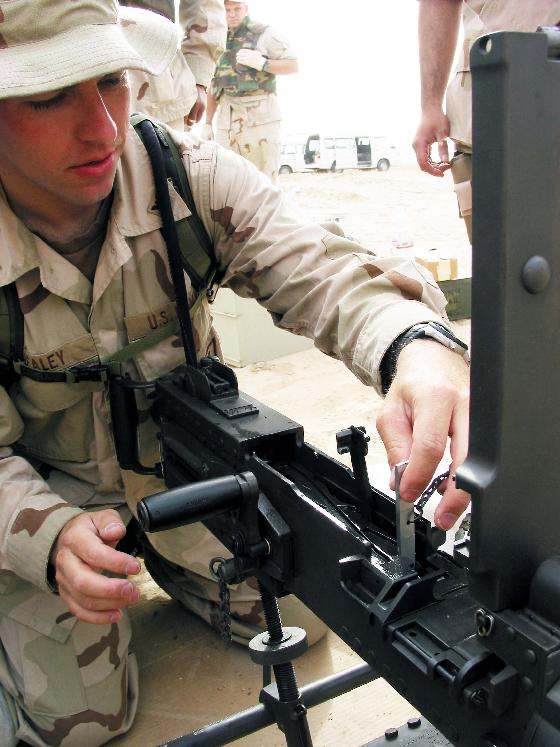 NAV2003041335 - Camp Patriot, Kuwait   April 12   (UPI) -- Gunner's Mate 3rd Class Jeff Healey, 23, from Albuquerque, N.M., tests the barrel alignment of the M2 .50 caliber machine gun with the 'go-no go' key during a recent joint live fire exercise here.  Healey and others attached to Mobile Inshore Undersea Warfare Unit One Zero Nine (MIUW-109), homeported in Fort Worth, Texas, described the specifics of the M2 to 20 Kuwaiti security force personnel during a joint nation crew serve weapons familiarization training fire.  MIUWU-109 is one of the key all-reserve units attached to Naval Coastal Warfare Group One (NCWG-1) forward deployed to handle force protection responsibilities at Camp Patriot. Camp Patriot is home to nearly 3,000 active duty and reserve Sailors, Soldiers, Marines, Airmen and Coast Guardsmen forward deployed in support of Operation Iraqi Freedom.  Operation Iraqi Freedom is the multi-national coalition effort to liberate the Iraqi people, eliminate Iraq's weapons of mass destruction and end the regime of Saddam Hussein.        dg/Joseph Krypel/U.S. Navy    UPI