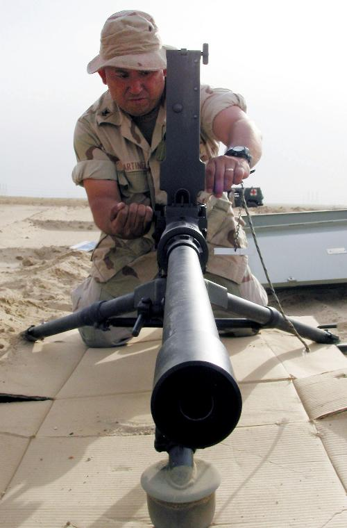 NAV2003041334  - Camp Patriot,  Kuwait   April 12  (UPI) -- Gunner's Mate 2nd Class Miguel Martinez, 34, from Dallas, Texas, tests the barrel alignment of the M2 .50 caliber machine gun with the 'go-no go' key during a recent joint live fire exercise.  Martinez and others attached to Mobile Inshore Undersea Warfare Unit One Zero Nine (MIUW-109), homeported in Fort Worth, Texas, described and showed the specifics of the M2 to 20 Kuwaiti security force personnel during a joint nation crew serve weapons familiarization training fire.  MIUWU-109 is one of the key all-reserve units attached to Naval Coastal Warfare Group One (NCWG-1), forward deployed to handle force protection responsibilities at Camp Patriot.  Camp Patriot is home to nearly 3,000 active duty and reserve Sailors, Soldiers, Marines, Airmen and Coast Guardsmen forward deployed in support of Operation Iraqi Freedom.  Operation Iraqi Freedom is the multi-national coalition effort to liberate the Iraqi people, eliminate Iraq's weapons of mass destruction and end the regime of Saddam Hussein.       dg/Joseph Krypel/U.S. Navy   UPI
